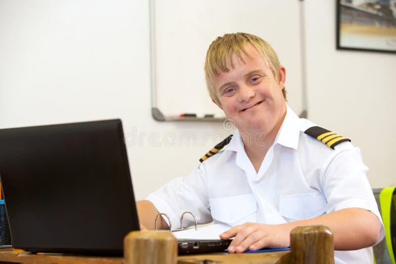Stående av barn som är pilot- med Down Syndrome på skrivbordet. fotografering för bildbyråer
