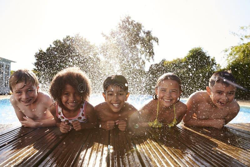 Stående av barn som har gyckel i utomhus- simbassäng arkivfoto