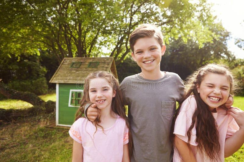 Stående av barn som står i trädgård bredvid lekstuga arkivfoton