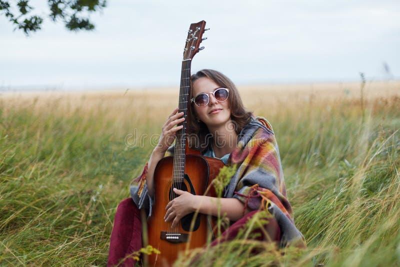 Stående av begåvat kvinnligt musikersammanträde på grönt gräs med gitarren som har det fundersamma uttryckt som beundrar naturen  royaltyfria foton
