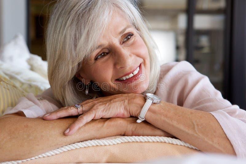Stående av bekvämt sammanträde för äldre kvinna på soffan royaltyfria foton
