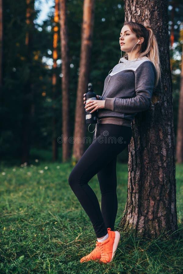 Stående av benägenheten för träningsoverall för nätt passformidrottskvinna den bärande mot trädet som lyssnar till musik i hörlur fotografering för bildbyråer