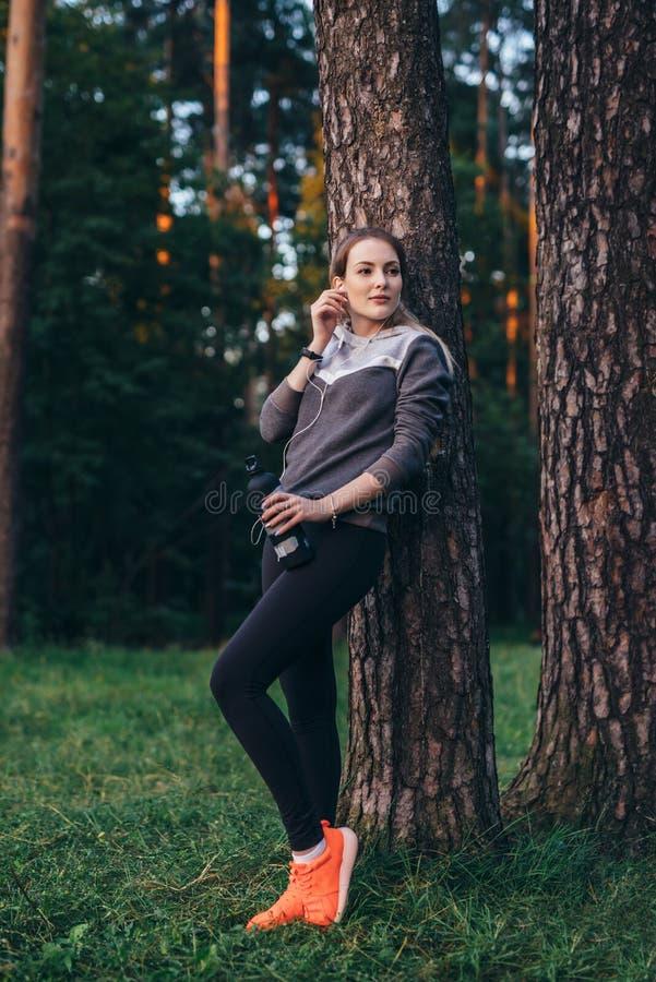 Stående av benägenheten för träningsoverall för nätt passformidrottskvinna den bärande mot trädet som lyssnar till musik i hörlur royaltyfria foton
