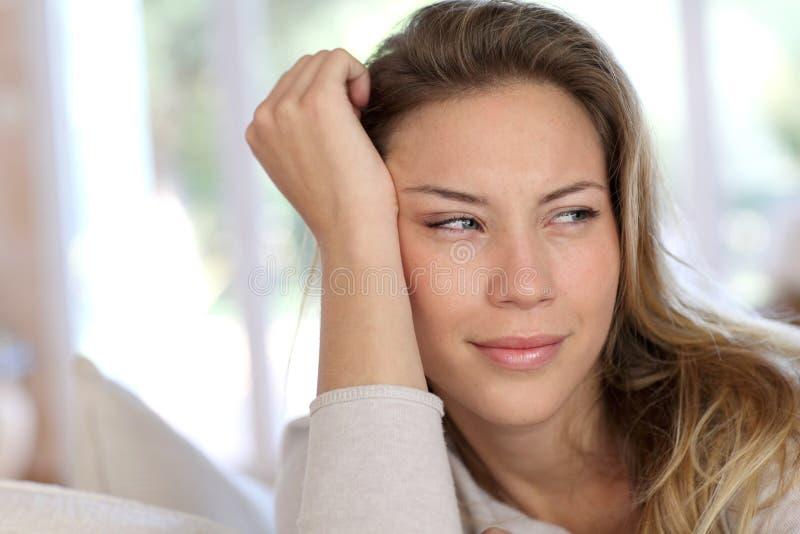 Stående av benägenheten för ung kvinna på soffan arkivbild