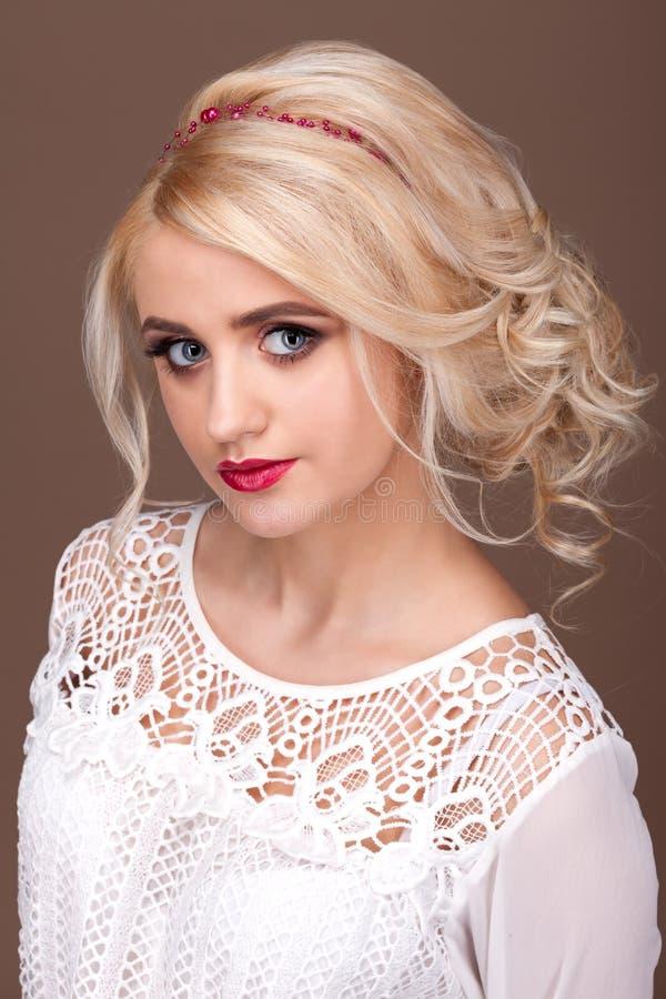 Stående av blondinen på en brun bakgrund arkivfoton