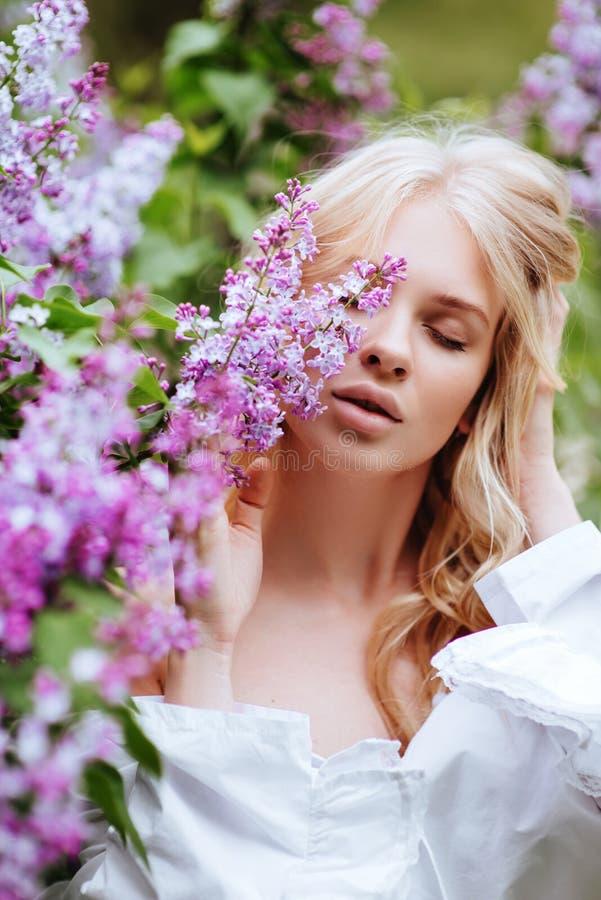 Stående av blondiner för en flicka med den lila busken arkivbilder