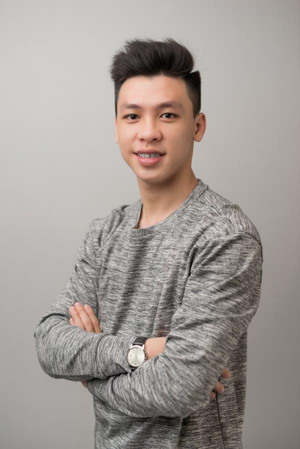 Stående av bra se den asiatiska mannen över grå bakgrund royaltyfri foto