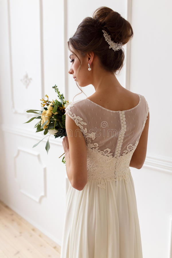 Stående av bruden i en bröllopsklänning med en bukett arkivfoton