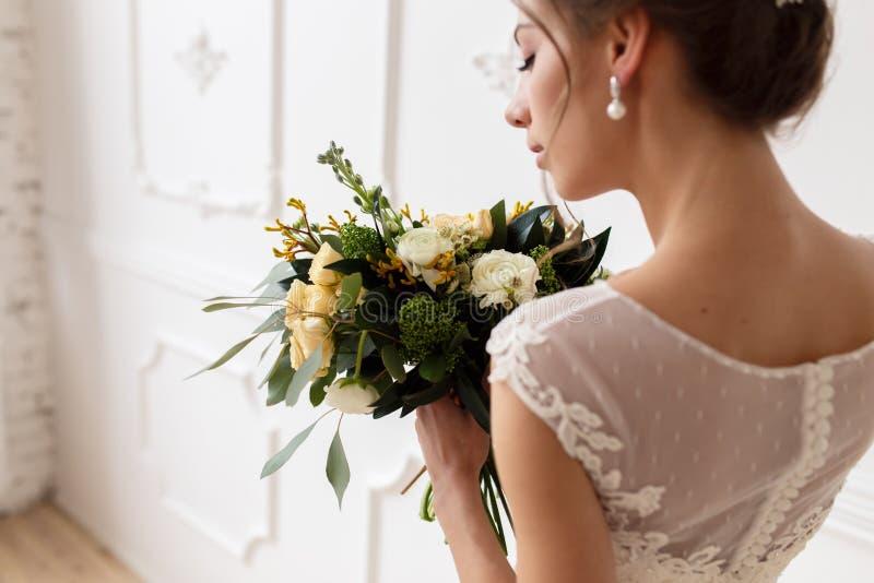Stående av bruden i en bröllopsklänning med en bukett royaltyfri foto