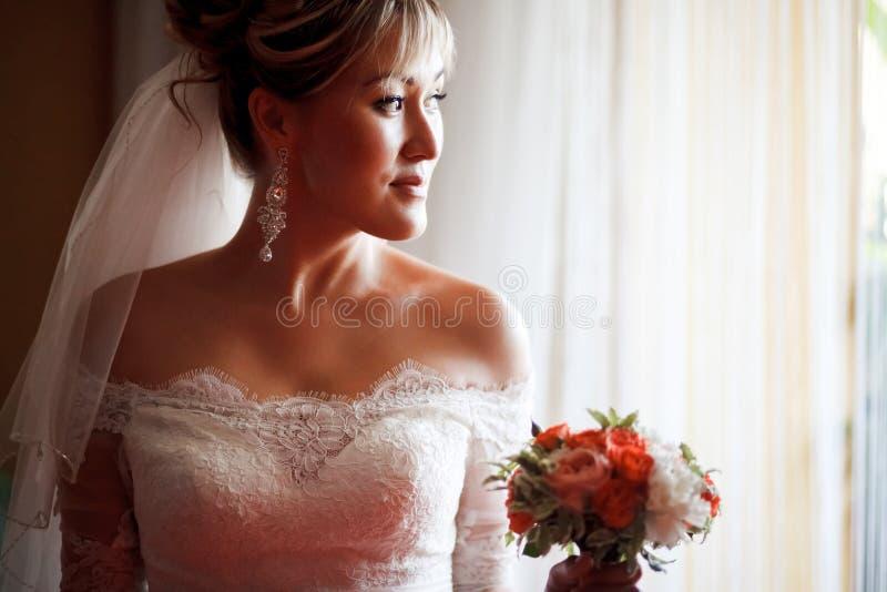Stående av bruden i profil med bröllopbuketten bredvid fönster royaltyfri fotografi