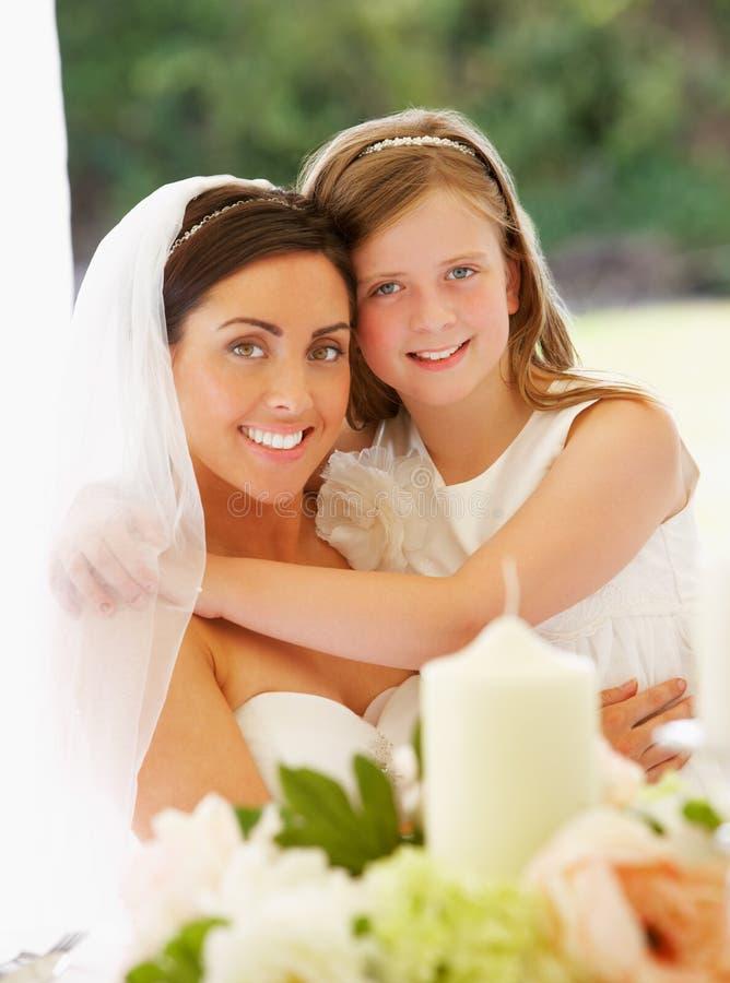 Stående av bruden med brudtärnan i stort festtält på mottagandet royaltyfri foto