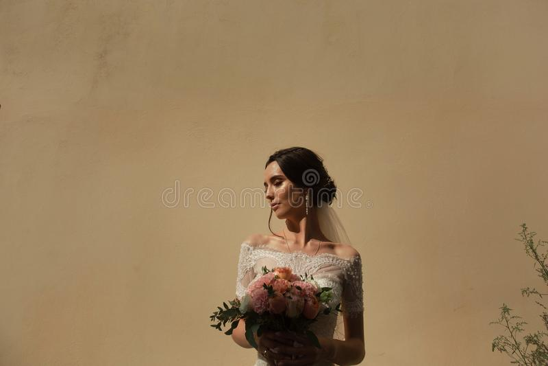 Stående av bruden med en grupp av blommor på bakgrunden av väggen royaltyfria foton