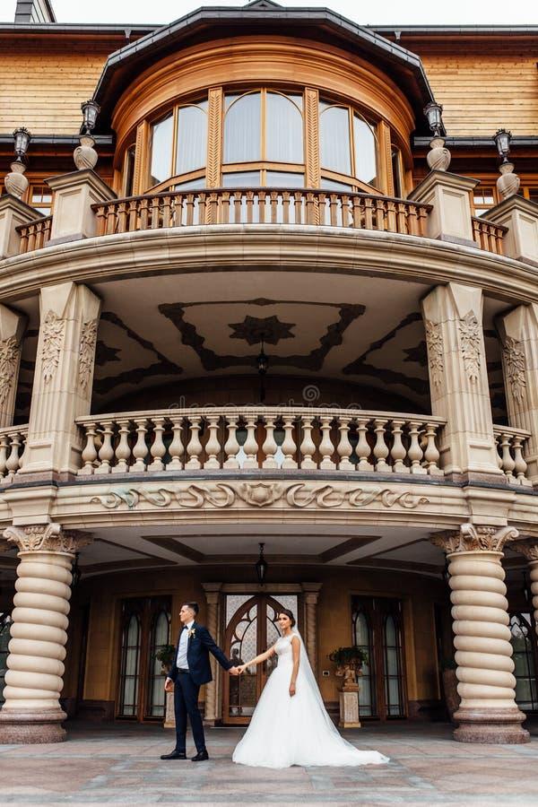 Stående av bruden och brudgummen nära byggnaden, ett förälskat par arkivbilder