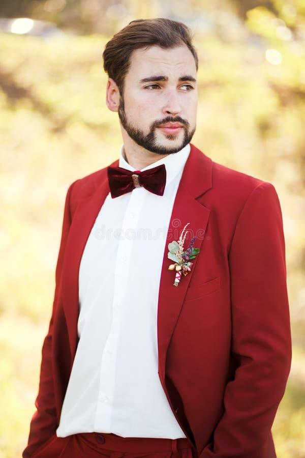 Stående av brudgummen, röd dräkt med en knapphålblomma Gifta sig i stilmarsalafärg royaltyfri foto