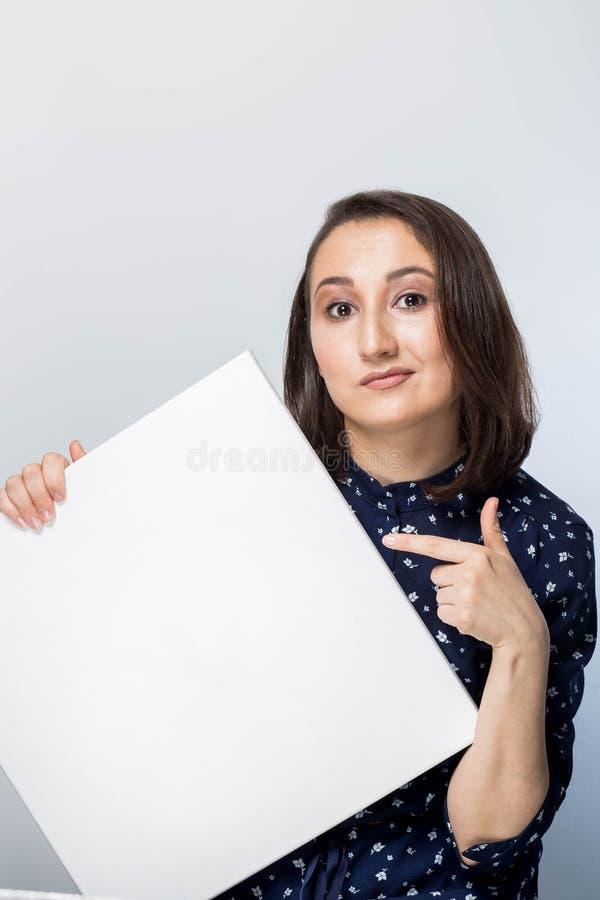 Stående av brunetten med annonsen som ser kameran, håll en affisch och punkter till honom På en vit bakgrund royaltyfri bild