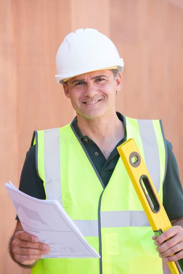 Stående av byggnadsarbetaren On Building Site med husplan arkivfoto