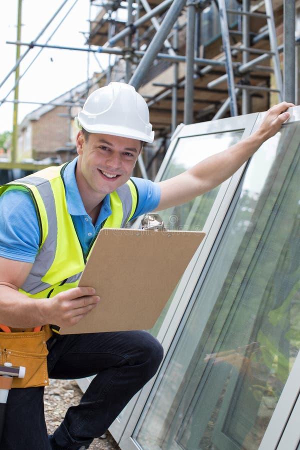 Stående av byggnadsarbetaren Preparing To Fit nya Windows fotografering för bildbyråer
