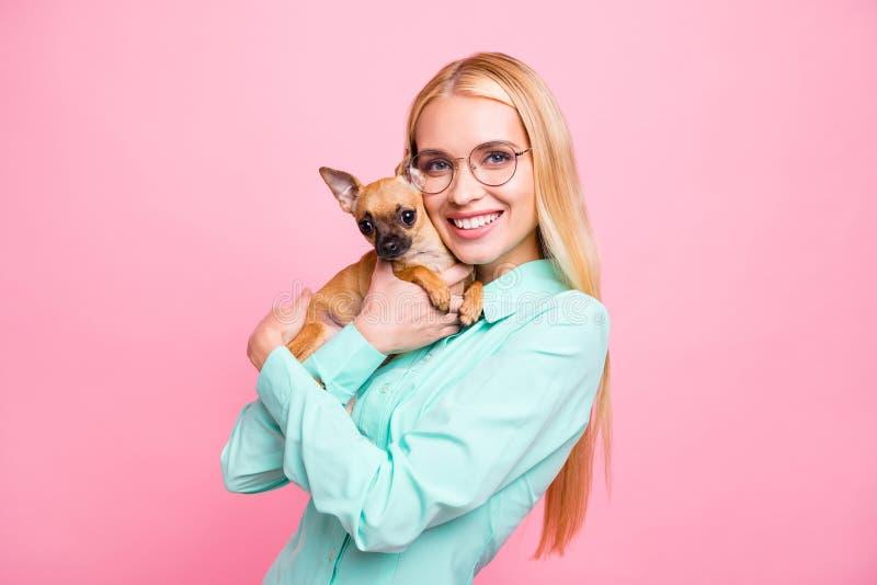 Stående av charmig damholdinh hennes husdjur som ser med för mintkaramellfärg för stråla leende som den bärande skjortan isoleras arkivbild