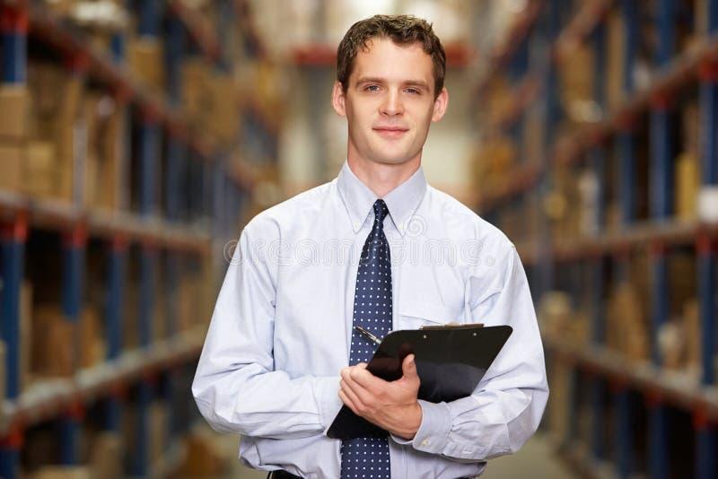 Stående av chefen i lager med clipboarden arkivfoton