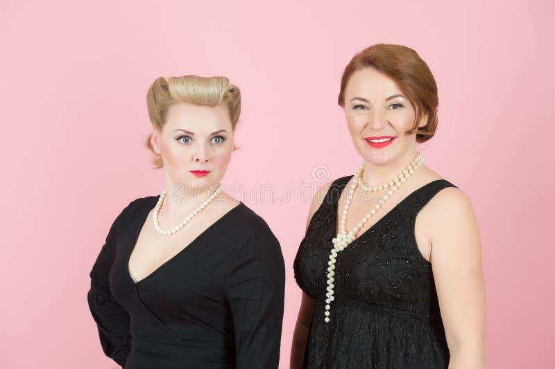 Stående av damer i svart klänning i amerikansk stil på rosa bakgrund royaltyfria bilder