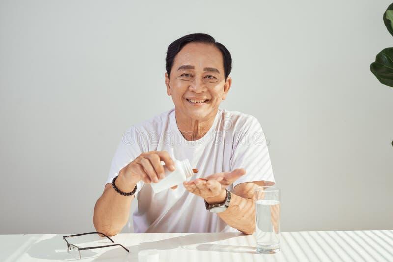 Stående av den äldre asiatiska mannen som tar medicin varje dag royaltyfri foto