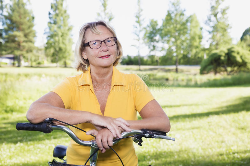 Stående av den äldre kvinnan med en cykel som tar ett avbrott arkivfoto