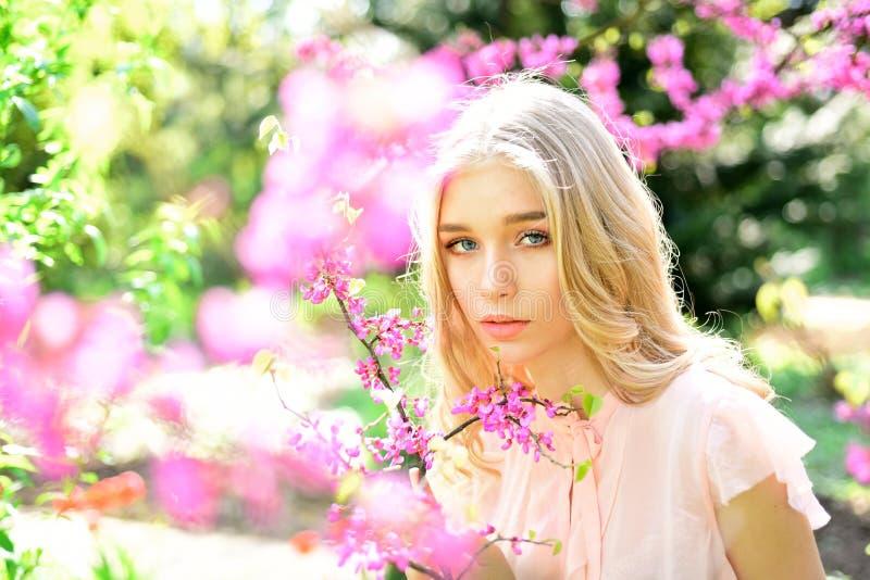 Stående av den älskvärda blonda flickan på naturlig bakgrund Den nätta unga kvinnan med blåa ögon som poserar bredvid att blomma, royaltyfri foto