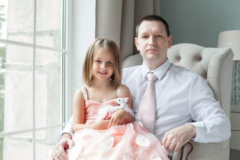 Stående av den älskvärda dottern som ler och sitter royaltyfria bilder