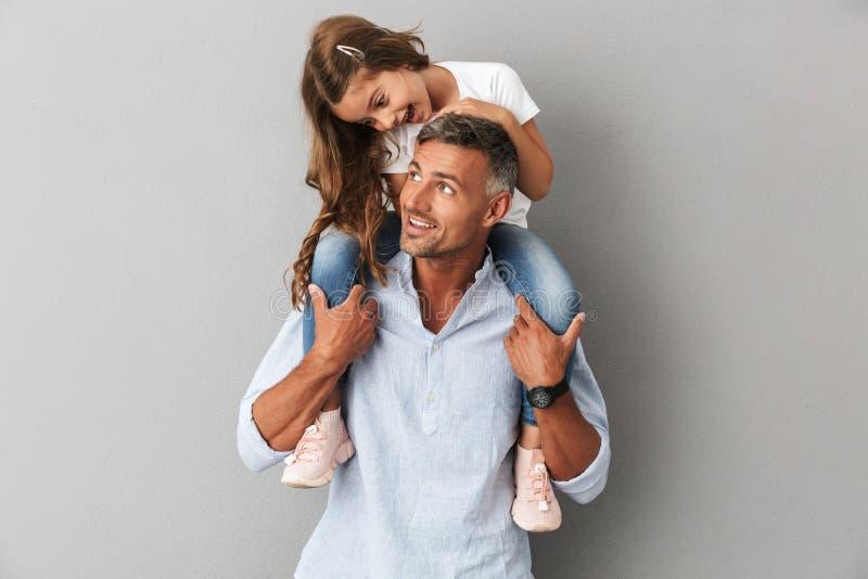 Stående av den älskvärda dottern som ler och sitter på halsen av H royaltyfri fotografi
