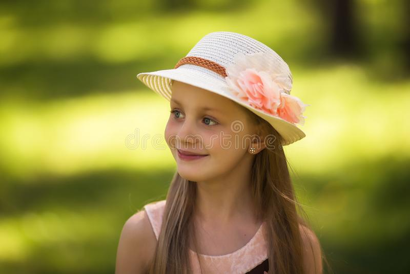 Stående av den älskvärda flickan i en sugrörhatt i parkera arkivfoto