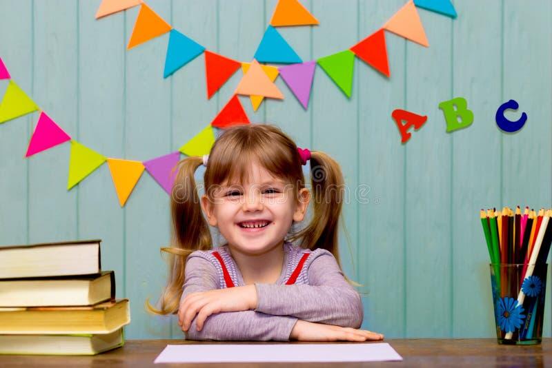 Stående av den älskvärda flickan i klassrum Litet skolflickasammanträde på ett skrivbord och studera royaltyfri bild