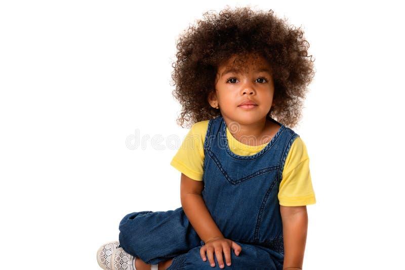 Stående av den älskvärda lilla flickan för afrikansk amerikan som sitter och ser till kameran som isoleras på vit bakgrund arkivfoto
