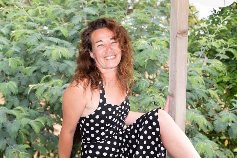 Stående av den åldriga brunettkvinnan för lycklig härlig mitt i vitt svart koppla av för klänning som är utomhus- fotografering för bildbyråer