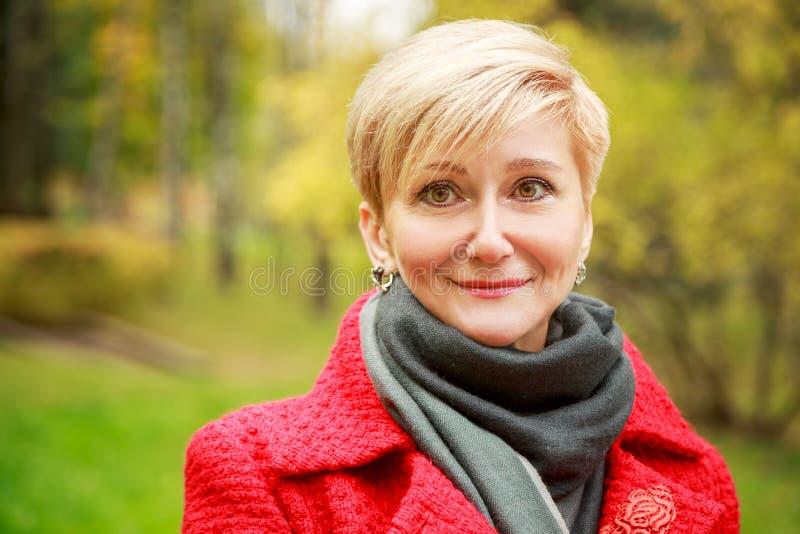 Stående av den åldriga kvinnan för mitt på Autumn Background royaltyfri foto