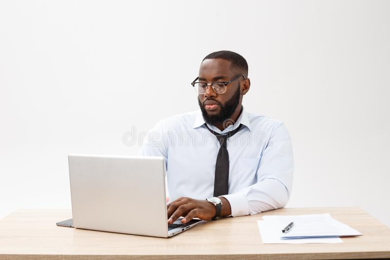 Stående av den afrikanska mannen som sleaping på hans arbetsplats på grå bakgrund royaltyfri bild