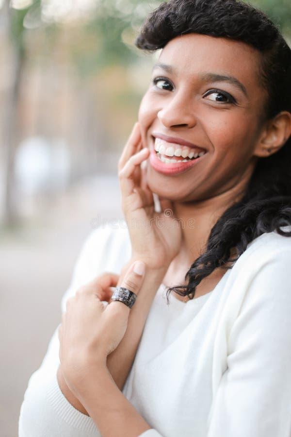 Stående av den afro amerikanska kvinnliga personen med hästsvansen och cirkeln som ler med vita tänder arkivfoto