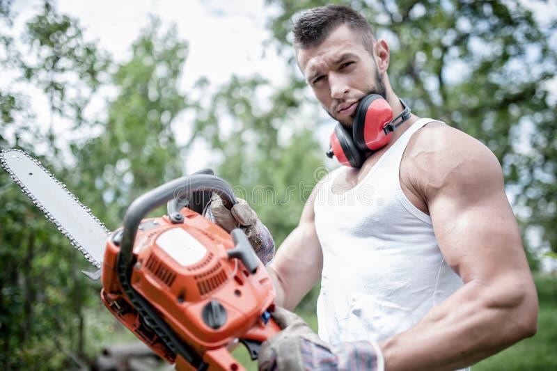 Stående av den aggressiva muskulösa manliga skogsarbetaren, inredningssnickare royaltyfri fotografi