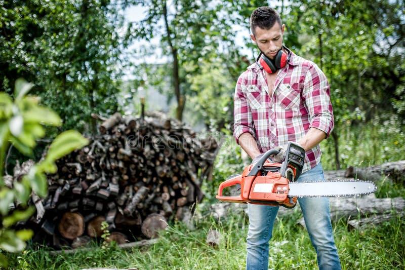 Stående av den aggressiva, muskulösa och idrotts- mannen med chainsawen arkivfoton