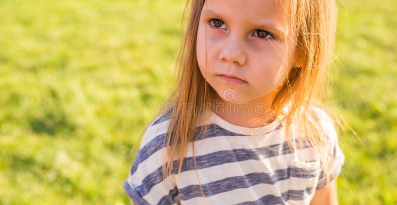 Stående av den allvarliga barnflickan i sommar i natur arkivbild
