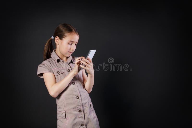 Stående av den allvarliga flickapekskärmen på mobiltelefonen arkivbild