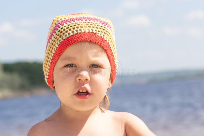 Stående av den allvarliga lilla flickan i hatt på sommarstranden som ser kameran royaltyfria foton