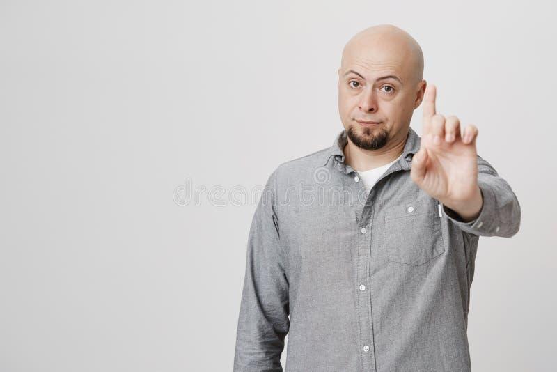 Stående av den allvarliga skäggiga grabben som förbjuder något, genom att lyfta hans pekfinger över vit bakgrund Mannen visar någ royaltyfri foto