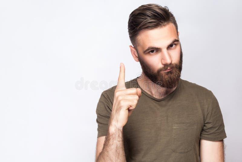 Stående av den allvarliga skäggiga mannen med varningsfingret och mörker - grön t-skjorta mot ljus - grå bakgrund arkivfoton