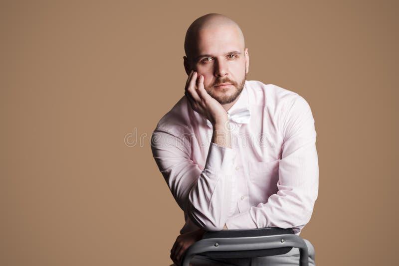 Stående av den allvarliga stiliga skäggiga skalliga mannen i ljus - rosa shir arkivfoto