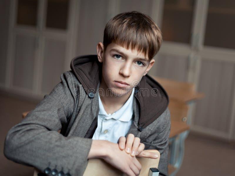 Stående av den allvarliga tonårs- pojken i grupp royaltyfria bilder