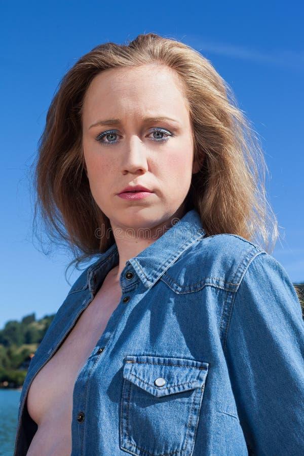 Stående av den allvarliga unga kvinnan i grov bomullstvillskjorta arkivbild