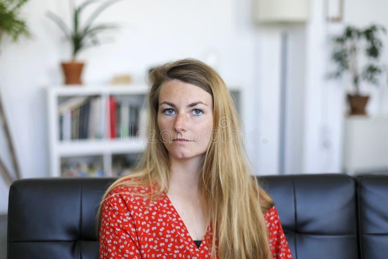 Stående av den allvarliga unga kvinnan som sitter på soffan royaltyfri bild