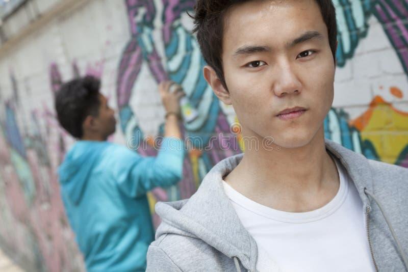 Stående av den allvarliga unga mannen med en kall inställning som ser kameran, sprejmålning för ung man i bakgrunden royaltyfria foton