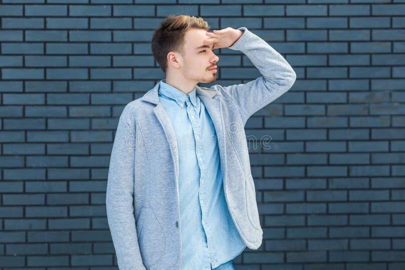 Stående av den allvarliga uppmärksamma stiliga unga blonda mannen i tillfällig stil som står med handen på pannan och bort ser fö arkivfoton