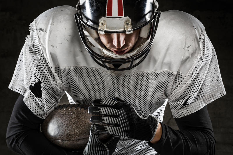 Stående av den amerikanska fotbollsspelaren som rymmer en boll royaltyfri bild